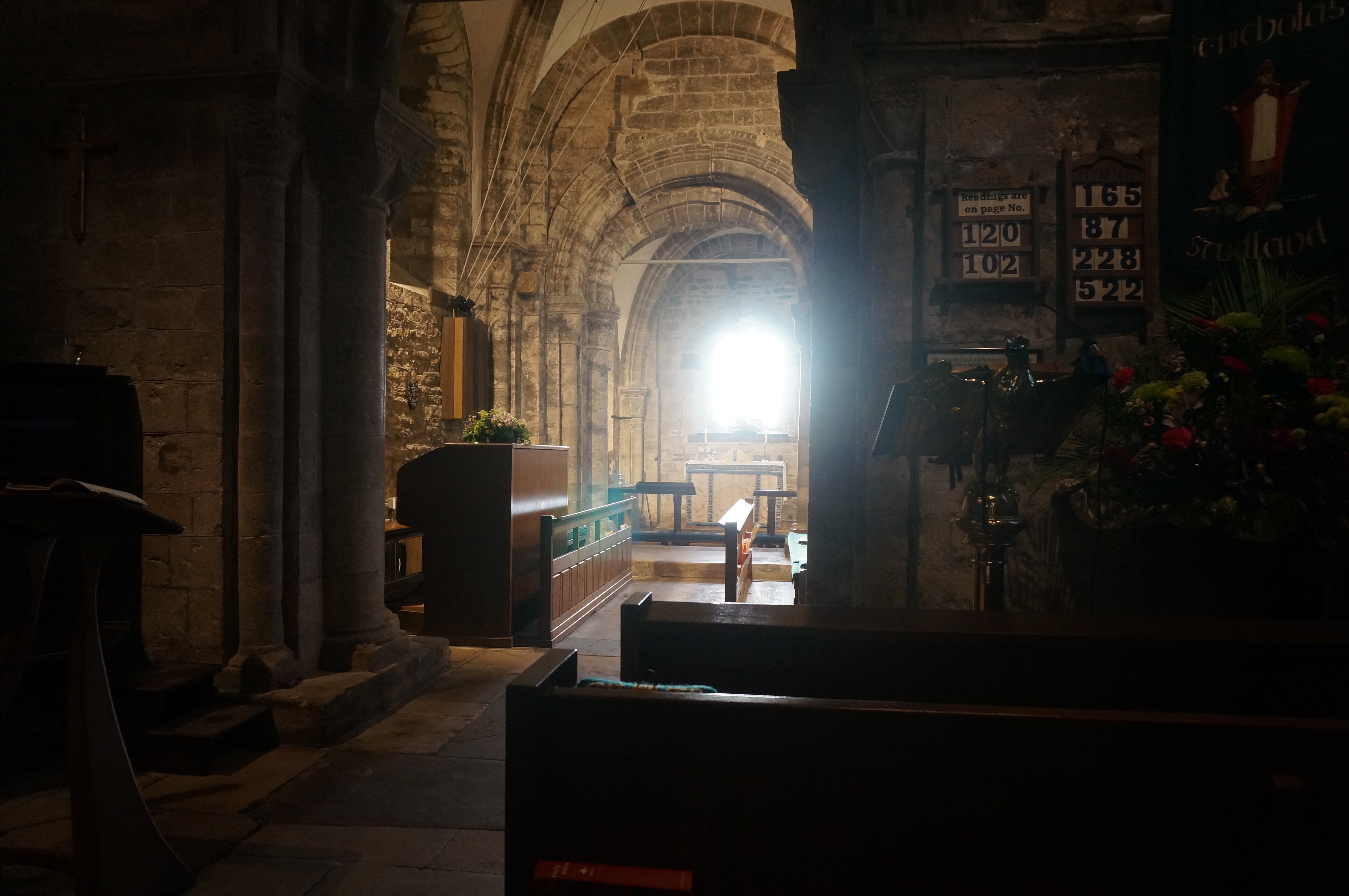 The sun shines directly through the East Window of St Nicholas' Church Studland in the early morning at Ascensiontide