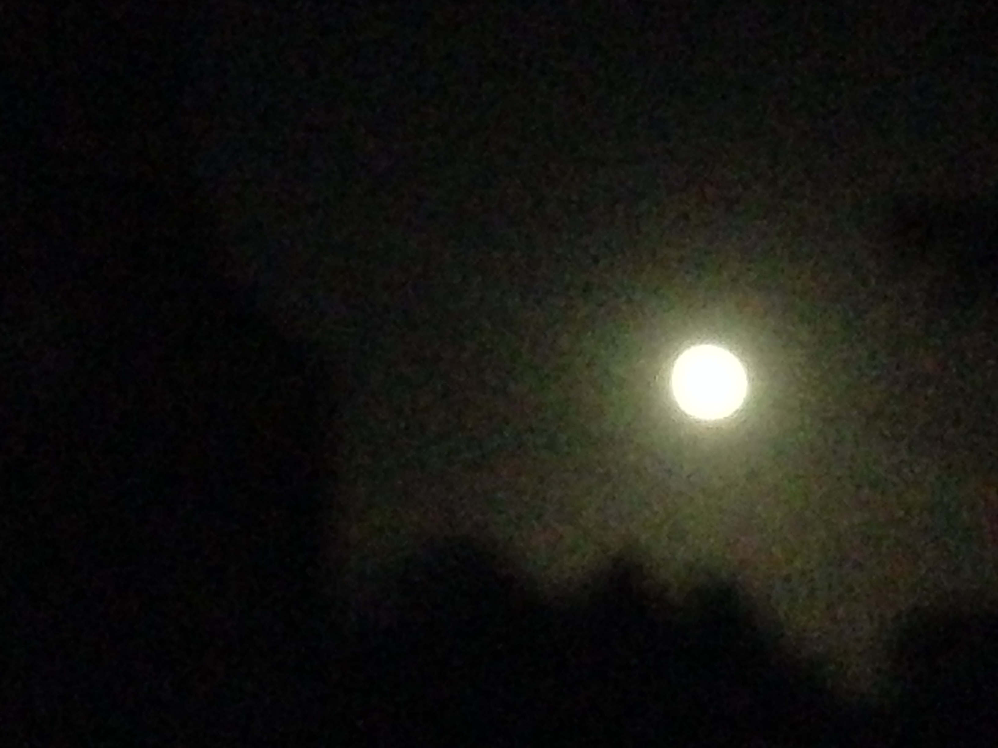 A bright moon shining through a fuzzy and dark sky last night from Studland Churchyard